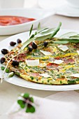 A hearty omelette with herbs, salami and olives