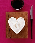 A heart-shaped Camembert, a knife and a glass of red wine