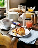 A breakfast of croissant, egg, juice and coffee on a wooden table