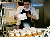 A woman sifting icing sugar on cream bun with almond paste, Sweden.