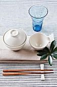 Gedeck mit Serviette, Essschalen, Trinkglas und Stäbchen (Asien)