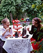 Two teenage girls sitting by a table in a park, Sweden.