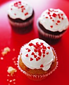 Cupcakes with cream frosting and red heart sprinkles