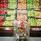 A small boy in a shopping trolley in front of a large display of apples