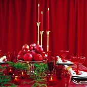 Festively set table with candlesticks in front of closed red curtain