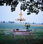 Romantisches Abendessen im Freien mit Kerzenleuchter an Baum gehängt