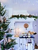 Geschmückter Weihnachtsbaum mit brennenden Kerzen in Landhausküche und Geschirrstapel auf Herd