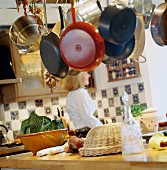 Pots and pans hanging from ceiling above vegetables on worksurface and view of woman in background