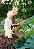 Mother and child next to raised vegetable bed in garden