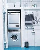 Waschmaschine und Trockner übereinander in Nische eines Badezimmers mit weissen Fliesen an Wand und blauen Mosaikfliesen an Boden