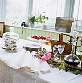 Coffee service and crystal carafe of liqueur on table with white tablecloth
