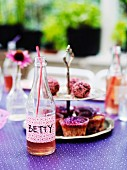 Bottle with lemonade and cupcakes on table