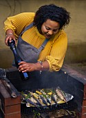 Woman cooking at barbecue grill using pepper mill