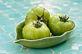 Three green tomatoes with water droplets in a ceramic dish