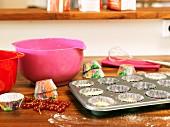 Muffinblech, Rührschüsseln und Papierförmchen auf Arbeitsplatte