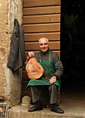 Italy, Tuscany, senior man holding traditional homemade ham