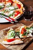 Pizza with tomato, cucumber, rocket and cream cheese