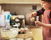 Child holding spoon with cake mix