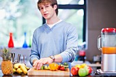 Young man in kitchen preparing fruit drink