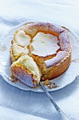 Baked cheesecake with icing sugar, one portion cut