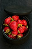 Fresh organic strawberries in a black ceramic dish