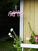 Von Decke abgehängte Wäschespinne in Rosa vor Hausecke mit Blumen