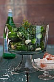 Salted cucumbers in glass jar with garlic and pink salt