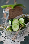 Salted cucumbers in glass bowl with bread and vodka