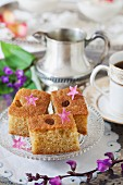 Samolina cake on a silver tray with cup of coffee and flowers