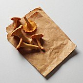 Five chanterelles on a brown paper bag