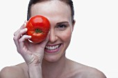Young woman covering eye with red tomato