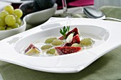 Ajoblanco (cold garlic and almond soup, Spain) garnished with grapes and figs