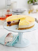 Lemon and blueberry cheesecake on a cake stand, slices removed
