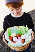 A boy holding a basket with painted eggs.