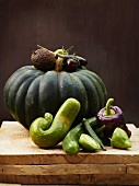 A still life of green vegetables, with squash, courgette, okra, cucumber and a pepper