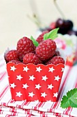 Fresh raspberries in red cardboard punnet with pattern of white stars