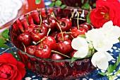 Kirschen und weisse Blüten in roter Glasschüssel
