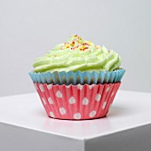 A cupcake with pistachio icing and colourful sugar balls