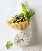 A pastry case filled with vegetables and mint