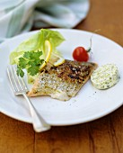 Pan-fried salmon fillet with herb butter and a salad garnish