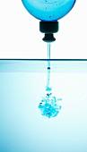 Blaues Spülmittel fliesst ins Wasser