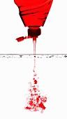 Rotes Spülmittel fliesst ins Wasser