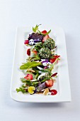 A salad of flowers in rose honey vinaigrette with goat's cheese balls