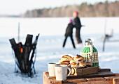Tisch mit Thermoskanne, Tassen und Gebäck im Winter