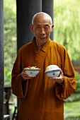 A monk with a bowl of rice and a bowl of vegetables