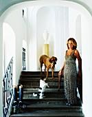 Frau im Abendkleid mit Hunden auf Treppe vor Nischen mit Rundbögen in herrrschaftlichem Treppenhaus