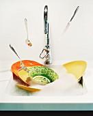 Besteck fällt in Spülbecken mit Abwaschwasser & Tellern