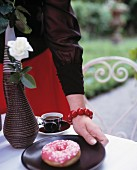 A woman putting a plate with a doughnut on it on a table in the garden