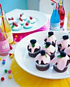 A table at a children's party with mini cakes and bottles of pop