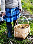 Girl standing in woods next to chip wood basket of mushrooms